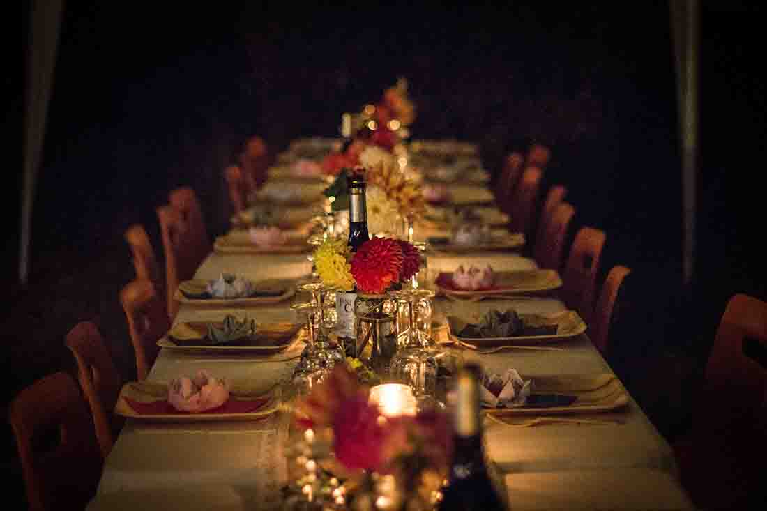 a dimly lit long table with food arranged on it