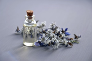 lavender oil in a bottle next to lavender blossoms