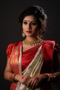 indian bride wearing a red saree and lots of gold jewelry